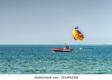 Unrecognizable people prepare on boat for parasailing, starting fly soon. Selective focus on parachute. Concept of vacation, extreme sports on a beach