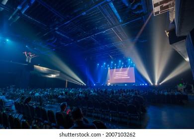 Unerkennbare Personen, die auf Stühlen vor der Bühne sitzen und während der Geschäftskonferenz im dunklen Saal mit leerem Bildschirm auf der Bühne sitzen