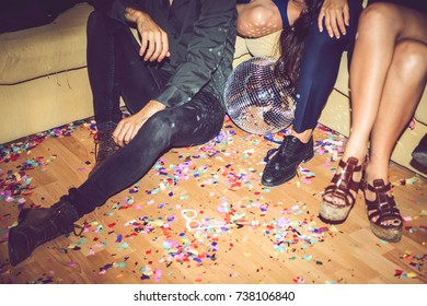 Unrecognizable people sitting on sofa and on dirty floor during private party.