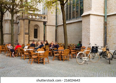 Unrecognizable people sitting on a terrace in Antwerp, Belgium, against the exterior of the cathedral in the city center, a typical relaxation moment in this touristic city