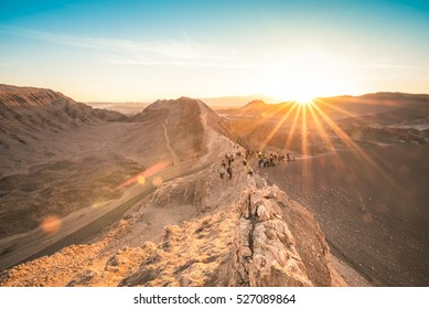"Unrecognizable people tourists watching sunset on rock formation mountain at "" Valle De La Luna "" in world famous Atacama desert in Chile - Adventure hiking trip to south latin america nature wonder"