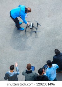 The unrecognizable person, camera operator and pilot with the controls panels teach to manage and use the drones of other new owners quadcopter UAV`s drone for commercial aerial photography.