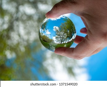 An unrecognizable person with a crystal ball in his hand with a landscape reflection