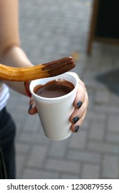 Unrecognizable person holding a churro - traditional Spanish fried-dough pastry with cup of hot chocolate for dipping. Street food concept. Selective focus.