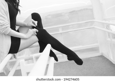 Unrecognizable person No face Woman legs in black pantyhose stockings indoor sits on railing Copy space for inscription Young adult girl wearing short dress and tightens a thin fingers woolen tights