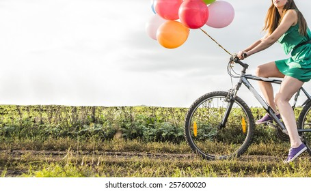 Unrecognizable person No face Young Girl in sexy dress with sunglasses riding bicycle flying air balloons on leash sky background Copy space for inscription SYMBOL OF EASE celebration tranquility