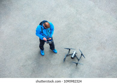 The unrecognizable person, pilot of the drone with the control panel prepares for the next flight on quadcopter UAV`s drone for commercial aerial photography.