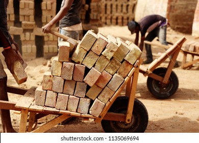unrecognizable person pushing cart field with bricks.