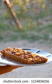 Unrecognizable person serving a pear and almond tart outdoor. Selective focus, illuminated by warm sunset light.