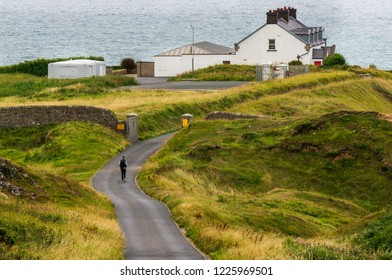 Unrecognizable person walking on an empty road towards a lighthouse building. Howth Cliff Walk in Dublin, Ireland.