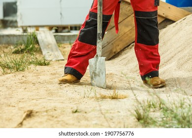 Unrecognizable person worker using shovel standing on industrial construction site, working hard on house renovation.