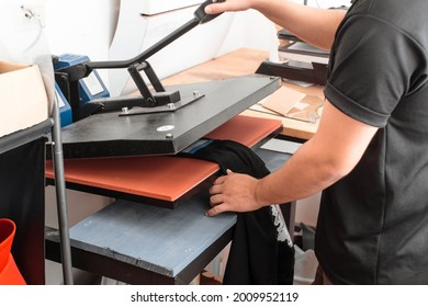 a unrecognizable person working on a iron sublimation. printing concept and graphic design.