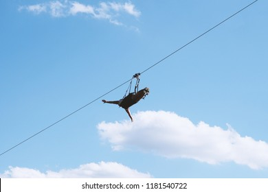 unrecognizable person ziplining with zip line, adventure sport concept, low angle view against sky
