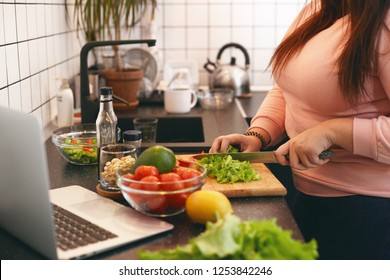 Unrecognizable plus size female standing at kitchen counter and cutting fresh organic vegetables on chopping board, making healthy low calories salad while watching movie online on laptop computer