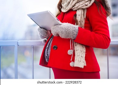 Unrecognizable pregnant woman in knitted clothes holding digital tablet, outside in winter weather