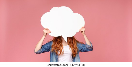Unrecognizable redhead female holding an empty speech bubble in front of her head, pink studio background, panorama with empty space