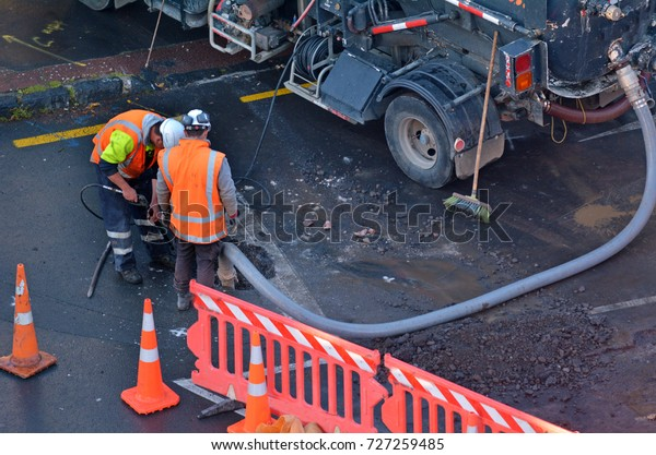 Unrecognizable road workers cleaning sewage in city street.