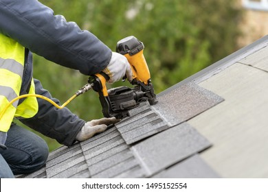 Unrecognizable roofer worker in uniform work wear using air or pneumatic nail gun and installing asphalt or bitumen tile on top of the roof under construction house