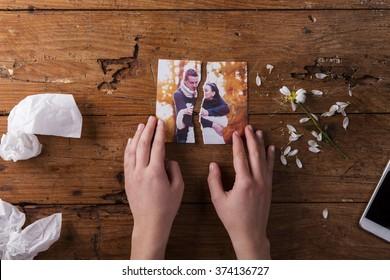 无法辨认的悲伤的女人拿着夫妇在恋爱撕裂的图片。