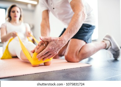 Unrecognizable senior physiotherapist working with a female patient.