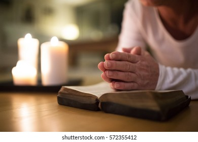 Unrecognizable senior woman praying, hands clasped together on h