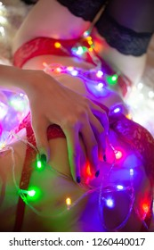 unrecognizable sensual young aroused woman in lingerie and stockings lying on bed with multicolored garland lights