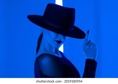 Unrecognizable sexy woman runs finger across brim of hat in dark neon studio background with colored blue light. Femme fatale, stylish outfit of ballet dancer.