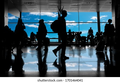 unrecognizable silhouettes of people in the airport lounge