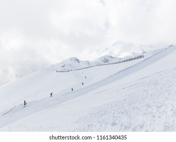 unrecognizable skiers ride on a ski slope, snow and clouds in the mountains Russia, Russia