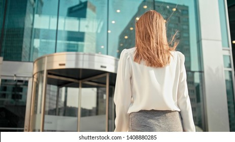 Unrecognizable Slender Caucasian Business Woman Manager in White Shirt is Entering into Office Building via Glass Revolving Door