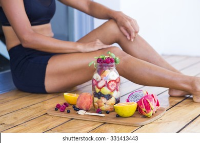 Unrecognizable sportive woman with a healthy breakfast in a mason jar