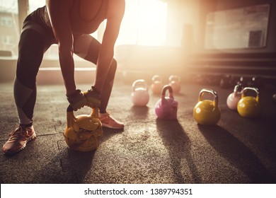 Unrecognizable sports women exercising with kettle bells in a gym