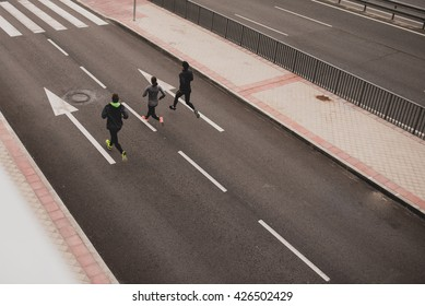 Unrecognizable sportspeople running fast along road.From above