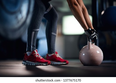 Unrecognizable sportswoman practicing with kettle bell on cross training in fitness center.
