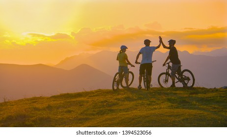 Unrecognizable sporty tourists high five after a successful evening bike ride in the golden lit mountains. Three cross country cyclists celebrate at sunset after a successful mountain biking adventure