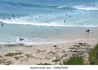 Unrecognizable surfers surfing on waves at Byron Bay Beach in New South Wales, Australia. It is one of the most popular waves surfing beach in Australia