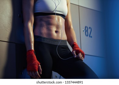 Unrecognizable sweaty sportswoman with abdominal muscles in gym's dressing room.
