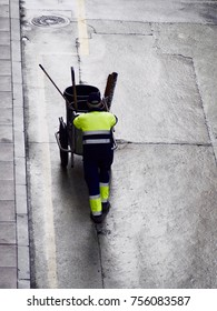 Unrecognizable sweeper taking trash trolley