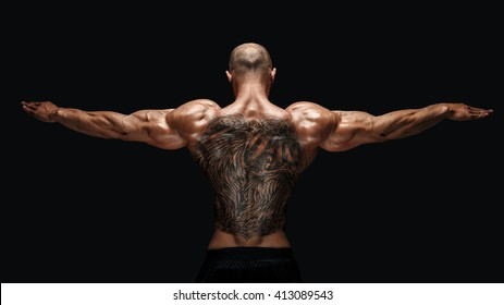 unrecognizable tattooed bodybuilder with outstretched arms on black background,Isolated.
