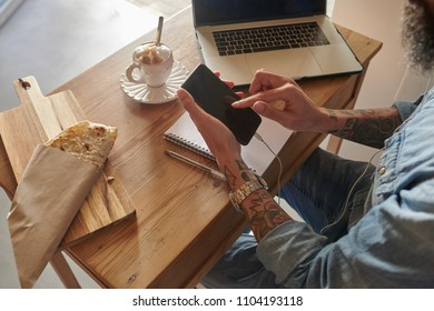 unrecognizable tattooed hipster in denim shirt and watch surfing the Net on his mobile phone while having lunch in cafe. Cappuccino coffee and tortillas on wooden board with laptop and notebook