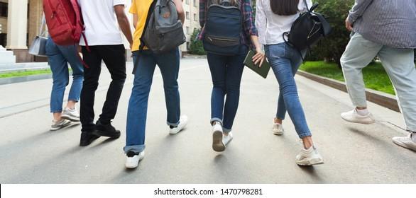Unrecognizable teenage students in high school campus walking at break, crop