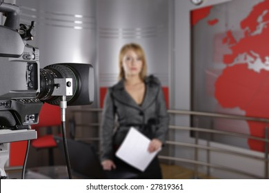 unrecognizable television news reporter in front of the video camera with documents in hand