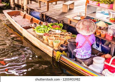 An unrecognizable Thai food peddler selling fruit and vegetables on her boat in the Damnoen Saduak floating market