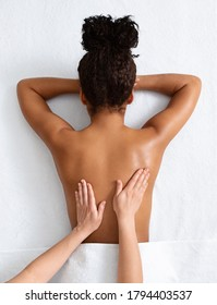 Unrecognizable therapist massaging african american woman back on white, top view