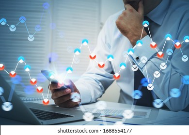 Unrecognizable thoughtful businessman using smartphone and laptop in blurry office with double exposure of blurry financial chart. Toned image