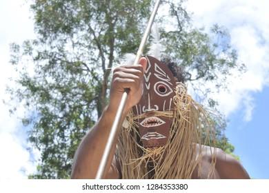 Unrecognizable Torres Strait Islander warrior man wearing a traditional mask dancing.