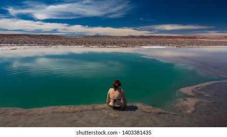 Unrecognizable tourist woman enjoys bright Baltinache Hidden lagoons salt lakes and Licancabur volcano in Atacama, Chile