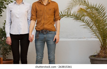 unrecognizable trendy young couple holding hands outdoors