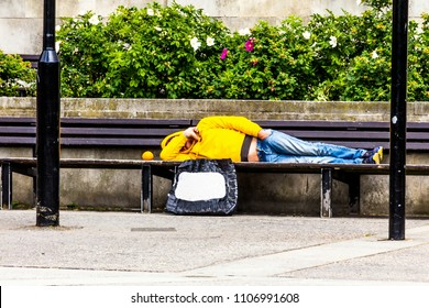 Unrecognizable unemployed in a yellow jacket with a hood and blue jeans lies on a park bench, covering his face with his hand