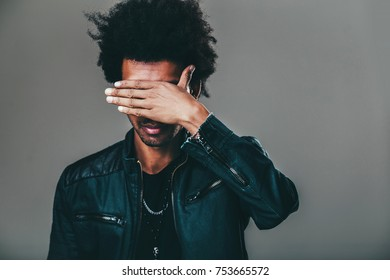 Unrecognizable unshaven African American man with tousled hair making facepalm gesture, covering eyes while feeling ashamed, standing against blank studio wall background with copy space for content